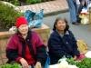 2 alte Asiatinnen, die auf dem Porirua Market am Samstag frueh auf dem Boden sitzend ihre Kraeutlein verkaufen